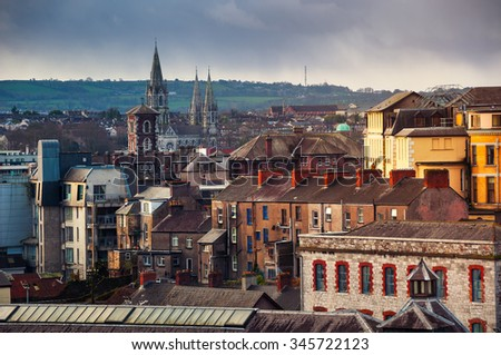 Aerial view of old part of Cork, Ireland with church and mountains at the background. Cloudy sky - stock photo