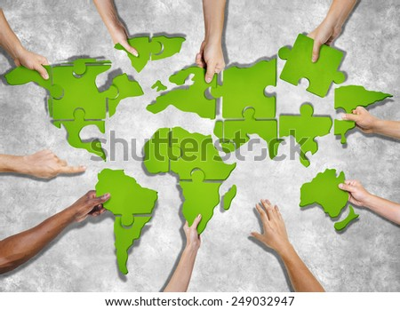 Aerial View of People Forming World Map with Puzzle Pieces - stock photo