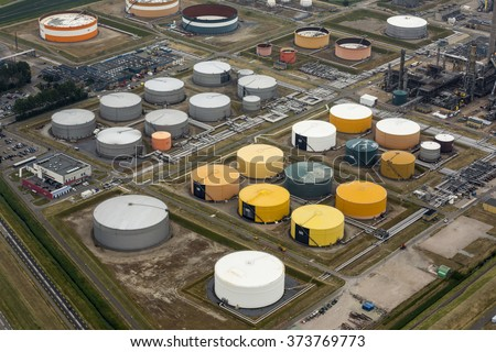 Aerial view of petrol industrial zone with yellow, green, white and grey storage tanks. It's the Zeeland Refinery in Vlissingen, Netherlands. - stock photo