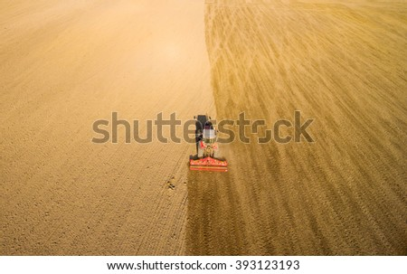 Aerial view of ploughed field with tractor sowing seeds of wheat. Industrial background on agricultural theme. - stock photo