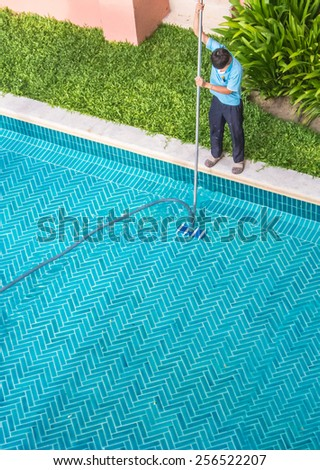 Aerial view of pool guy cleaning in the early morning.  Worker cleaning the pool. - stock photo