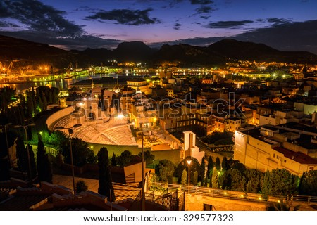 Aerial view of port city Cartagena in Spain with famous roman amphitheater. Beautiful sunset over the mountains. - stock photo