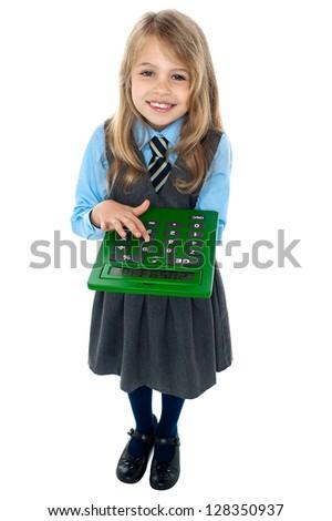 Aerial view of pretty schoolgirl in studio pressing key 6 on calculator. - stock photo