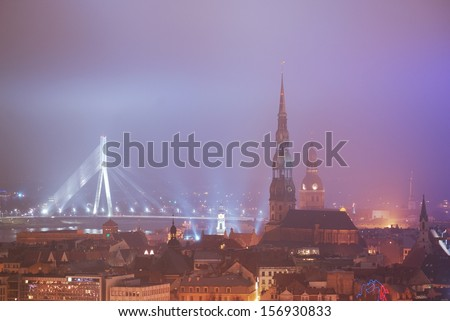 Aerial view of Riga St. Peters church by night in the fog - stock photo