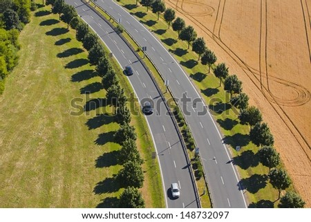 Aerial view of road between green meadow and field.  - stock photo