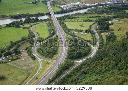 aerial view of road junction beside river - stock photo