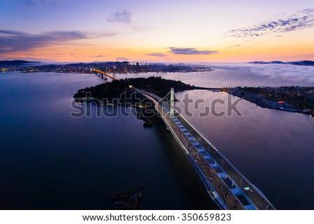 Aerial view of San Francisco Oakland Bay Bridge and Treasure Island at sunset, California, USA - stock photo