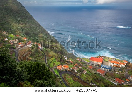 Aerial view of steep serpentine road from the mountains down to Porto Moniz town on the shore of Atlantic ocean. Madeira island, Portugal. - stock photo