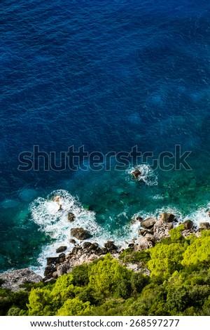 Aerial view of stony seashore with blue sea and fresh green vegetation - stock photo