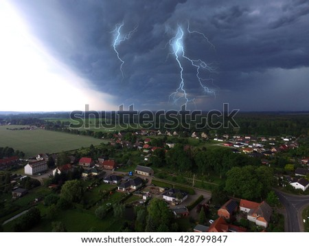 aerial view of storm over a smal village in germany with thunder and lightning  - stock photo