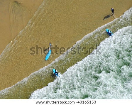 Aerial view of surfers at the water's edge - stock photo