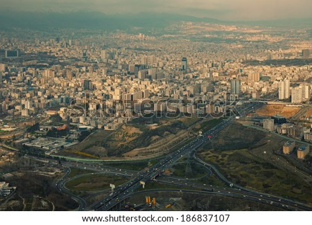 Aerial view of Tehran in a rainy day with ray of sunlight shining through clouds on the city. - stock photo