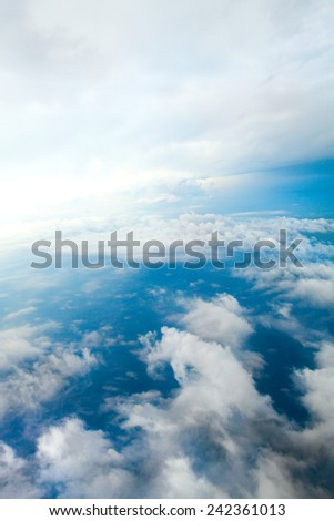 Aerial view of the blue skies and horizon with fluffy clouds and the earth below shot over Tennessee USA. - stock photo