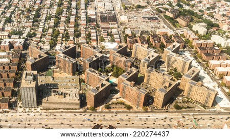 Aerial view of the Borough of Queens, New York, showing geometrically arranged and densely packed buildings and a multi-lane super highway - stock photo