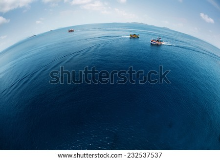 Aerial view of the calm tropical sea with ships on surface - stock photo