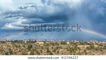 Aerial view of the city of Addis Ababa covered by a rainbow and dark clouds - stock photo