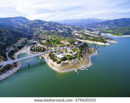 Aerial view of the earthfill dam (aka Embankment Dam) in Yermasoyia,Limassol,Cyprus. The bridge leading to the mountains, the water reservoir, artificial lake and the nature trails in Germasogia area. - stock photo
