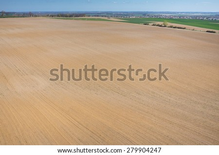 Aerial view of the large brown field in spring season - stock photo