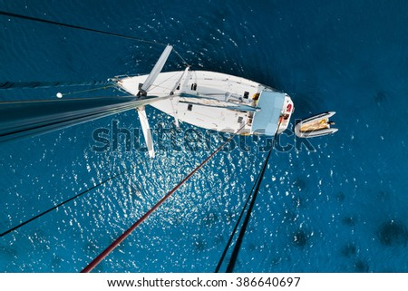Aerial view of the sailboat anchored in the tropical calm sea - stock photo