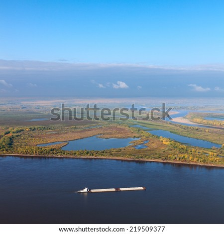 Aerial view of the ship which is pushing barge with load of breakstone on the great river in autumn. - stock photo
