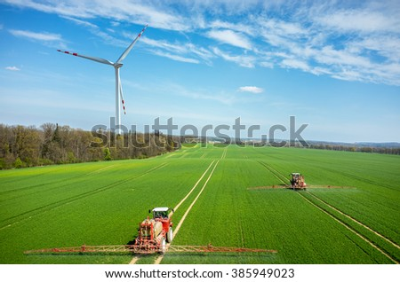 Aerial view of the tractors spraying the chemicals close to the windmill on the large green field - stock photo