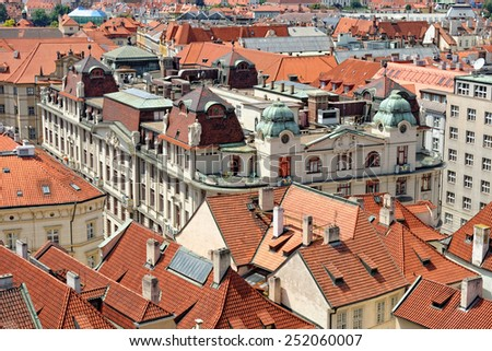 Aerial view of the traditional red roofs of the city of Prague, Czech Republic. The Prague  New City Hall is seen with its sculptures on the roof.  - stock photo