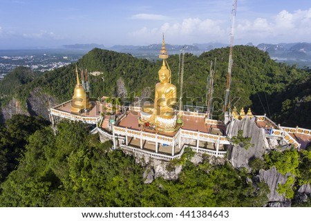 Aerial view of Tiger Cave Temple or Wat Thum Sua at Krabi province, Thailand. At the top of the mountain there is a large golden Buddha statue which is a popular tourist attraction. - stock photo