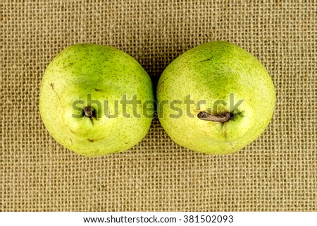 Aerial view of two green pears with brown stems - stock photo