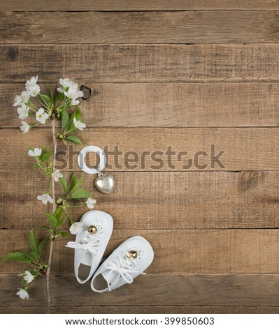 Aerial View of White Vintage Baby Shoes with Antique Teething Ring and White Flowers on Horizontal Rustic Wood Board Background with room or space for copy, text, your words, Vertical Warm toned - stock photo