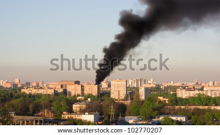 Aerial view on city fire - Heavy black smoke above the residential blocks polluting atmosphere and environment - stock photo
