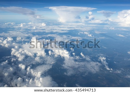 Aerial view on clouds and blue sky from airplane window - stock photo