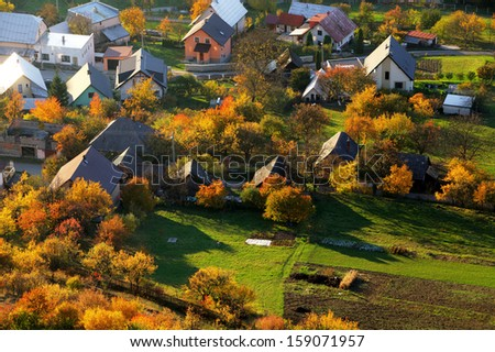 Aerial view on small town - colorful fields and trees in autumn, - stock photo