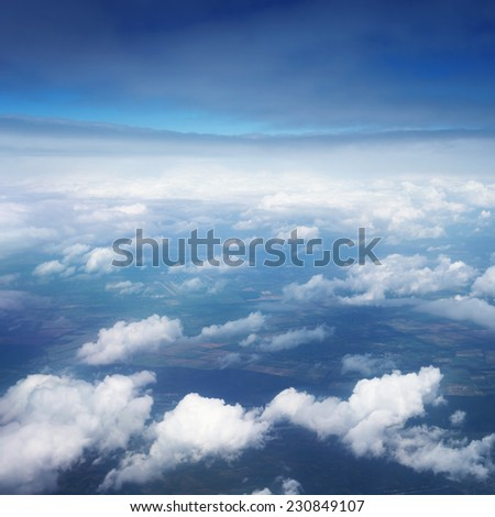 aerial view over the clouds on blue sky - stock photo