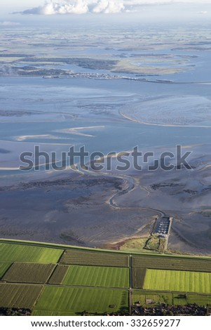 Aerial view over the shoreline, fileds and wetlanf of frisian island Ameland, The Netherlands - stock photo