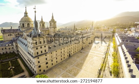 Aerial view Royal Monastery of San Lorenzo de El Escorial near Madrid, Spain against sun with strong sunbeam flare light  / STUNNING VIDEO AVAILABLE (UHD Quality) on my footage gallery. ID 9717071 - stock photo