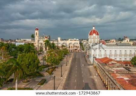 Aerial view to Jose Marti park with Town Hall and Cathedral of the Immaculate Conception lit by evening sun under heavy clouds shown on 5 May 2008 in Cienfuegos, Cuba - stock photo