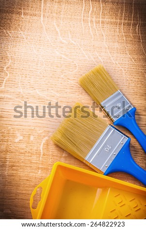 aerial view two paintbrushes with blue handles and yellow paint can on wooden board construction concept  - stock photo
