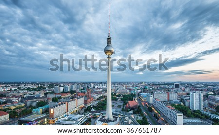 Aerial wide angle view of Berlin skyline with famous TV tower at Alexanderplatz and dramatic clouds in twilight during blue hour at dusk, Germany - stock photo