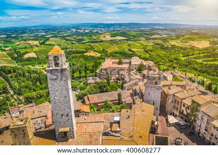 Aerial wide-angle view of the historic town of San Gimignano with Tuscan countryside on a sunny day with blue sky and clouds in summer, Tuscany, Italy - stock photo
