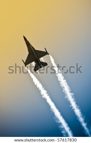 aerobatic military jet in a gradient sky leaving a smoke trail - stock photo