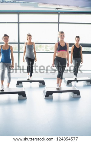 Aerobic group stepping in gym - stock photo