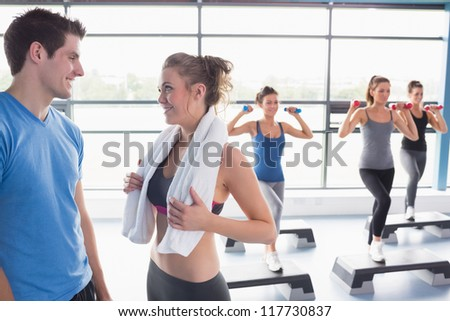 Aerobics class lifting weights while woman talking to trainer in gym - stock photo