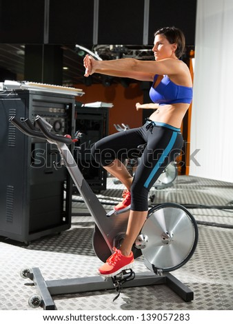 Aerobics spinning monitor trainer woman stretching exercises after workout at gym - stock photo