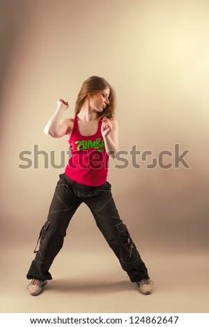 Aerobics/ zumba fitness woman dancing in studio. Active, energetic, joyful aerobic instructor in motion - stock photo