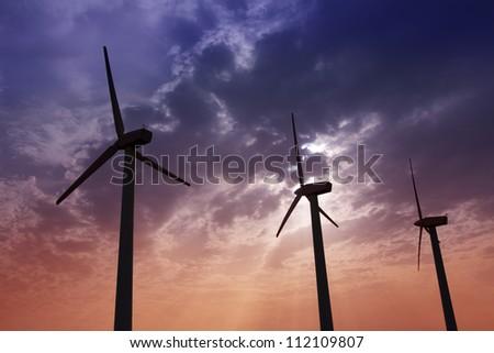 aerogenerator windmills on dramatic sunset sky green electric energy - stock photo