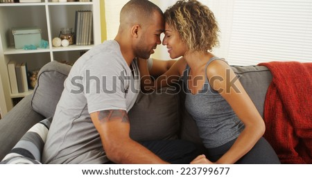 Affectionate african american couple talking on couch - stock photo