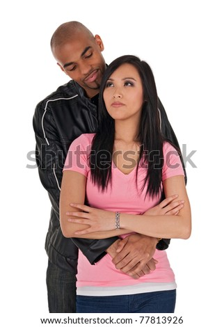Affectionate African American guy embracing sceptical-looking Asian girl. - stock photo