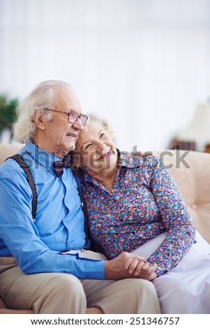 Affectionate aged couple in smart clothes having rest on sofa - stock photo