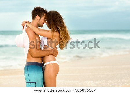 Affectionate couple embracing  on beach - stock photo