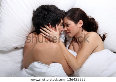 Affectionate couple kissing in bed - stock photo